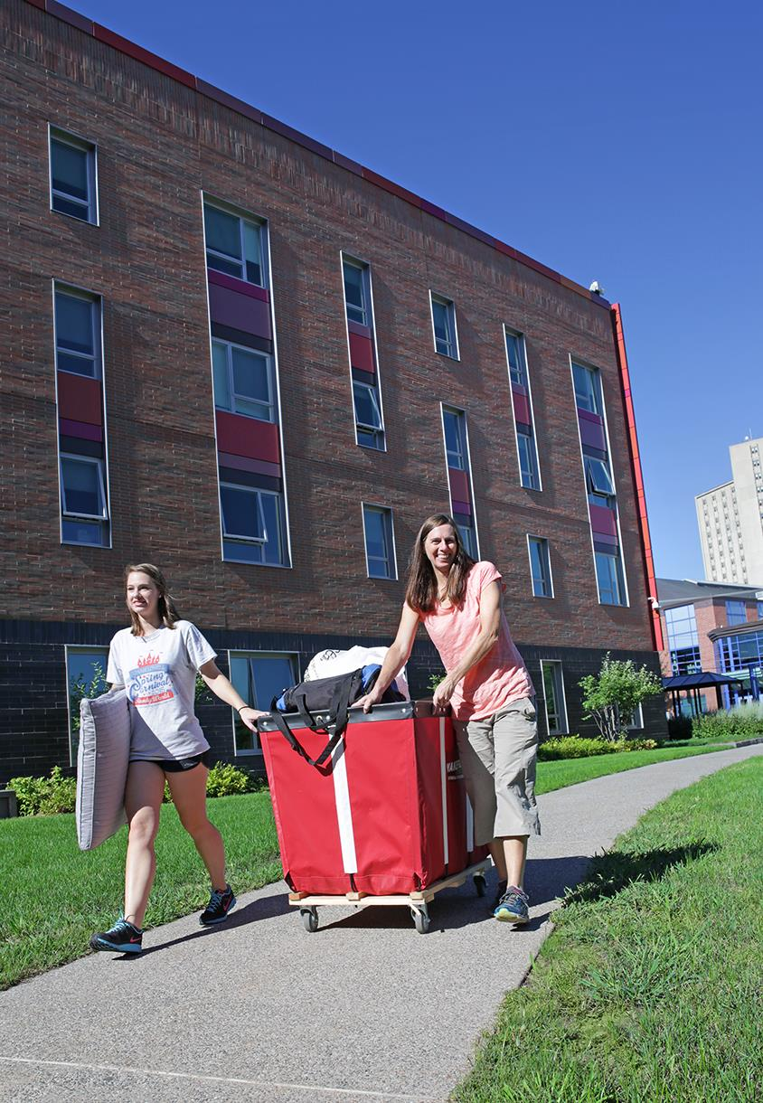 Student pulling bin with belongings along sidewalk with parent